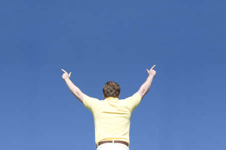 Man raises arms and points with his fingers under a blue sky
