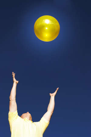 Man in a yellow shirt with his hands out worshipping the sun