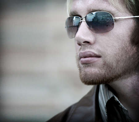 Young man in sunglasses and leather jacket, looks to the side Stock Photo