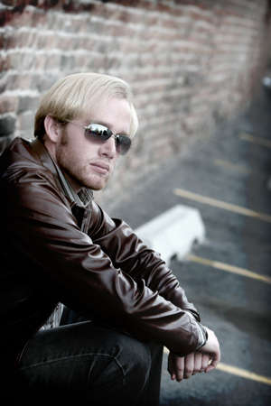 Young man with blonde hair and arms over his knees with sunglasses