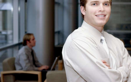 Young business man smiling looking forward with another business man in the background typing on laptop photo