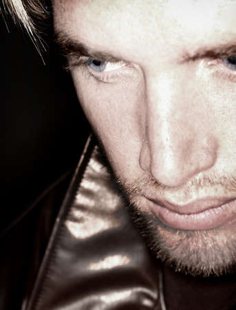 Blond hair and blue eye man looking off and down into the distance while wearing a leather jacket Stock Photo