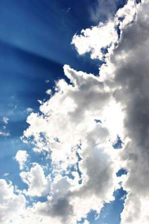 beaming: Rays of Sun beaming through clouds in the blue sky