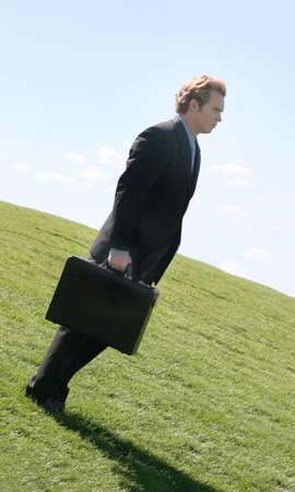 against all odds: Business man in black suit and blue shirt holding briefcase as he is looking downwards on a green grass hill against the blue sky Stock Photo