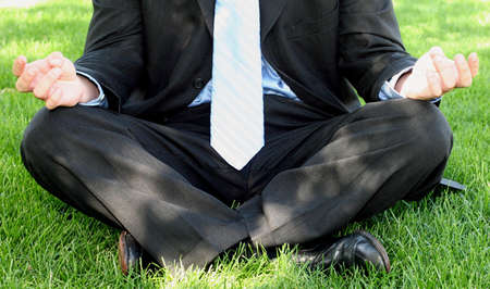 Business man in black suit and blue tie is in meditation stance on green grass