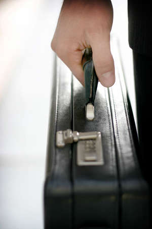 Business man grabbing briefcase with one hand photo