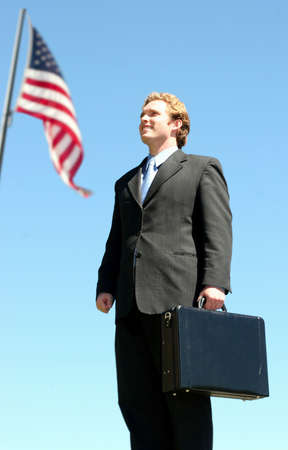 Business man in black suit carrying a briefcase posing next to an american flag against a blue sky