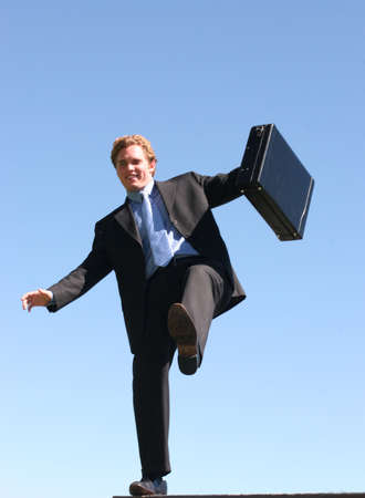 Business man in black suit and blue shirt, holding briefcase is balancing on one foot against the blue sky Stock Photo