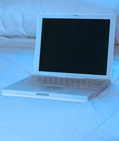 white laptop on top of bed