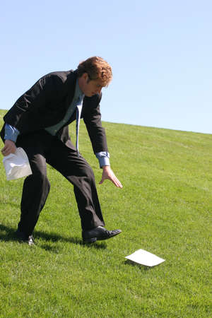 Business man walking down grassy hill trying to pick up his lost papers. Imagens