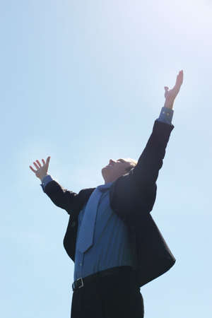 unanimous: Business man raising his hands up to the sky as he is smiling and dressed in a black suit in a blue shirt and tie Stock Photo