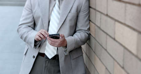 Business man in tan suit is holding and typing on his pda computer Stok Fotoğraf