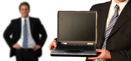 Business man in black suit, white shirt, and blue tie is holding his laptop with a black screen, and there is another business man in the background smiling Фото со стока