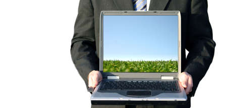 Business man with black suit, white shirt, and blue tie is holding his laptop that has a pic of green grass with blue sky Stock Photo