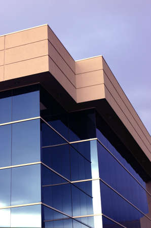Business building with blue windows and tan top Imagens