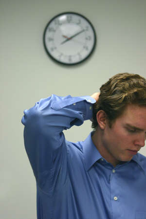 Business man in blue shirt has one behind his head with a clock in the background Imagens