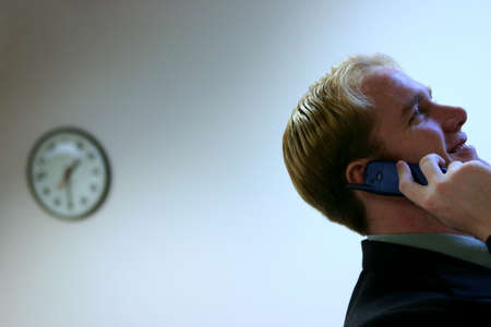 cultural artifacts: Business man with blond hair and blue eyes is holding a cell phone next to his ear with a clock in the background