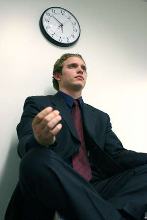 race for time: Business man in black suit, red tie, and blue shirt is in a state of pure meditation with a clock in the background