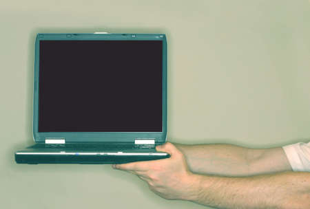 Business man is extending out his arms, holding a laptop with a black screen
