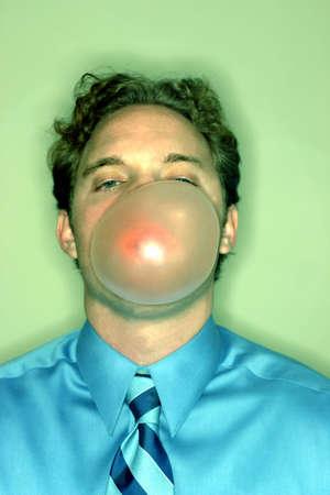 spunk: Negocios hombre vestido camisa azul y corbata azul est� soplando una gran burbuja con su goma de mascar