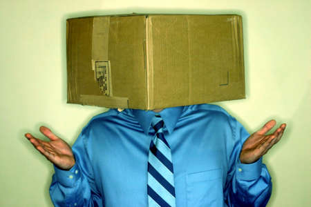 resourcefulness: Business man has his head in a carboard box with his hands held up in gesture of confusion Stock Photo