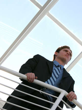 Business man with dark brown hair, blue shirt, blue tie, and black suit is holding a gaurd rail with a expression of vision