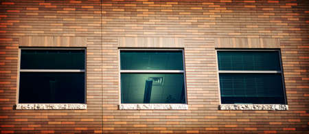 representations: Three windows in a brick building with the middle room lit up