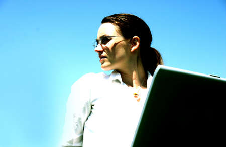Business woman with glasses and white shirt has laptop on her lap against a blue backdrop photo