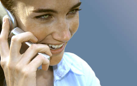Business woman with cellphone is smiling as she holds cellphone to her ear