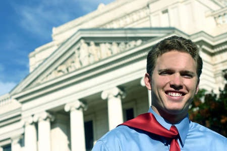 happy young man is leaving the courthouse with a blue shirt and red tie Stock Photo