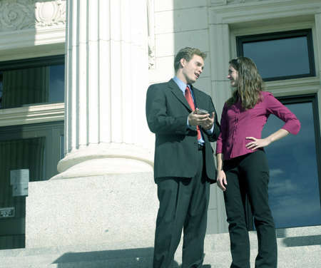 legal services: Successful man and woman are talking on the court steps with their pda