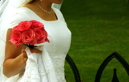 Bride is carrying her pink roses