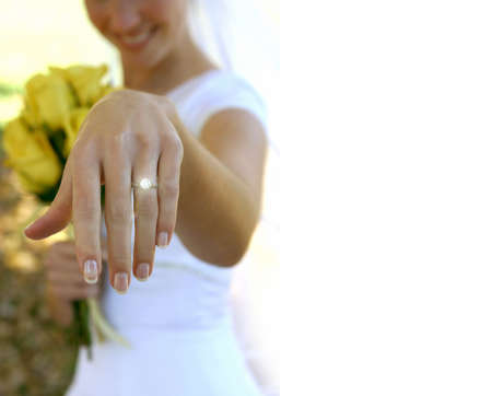 Wedding bride holds out her sparkling ring with yellow flowers in the background Stock Photo - 456891