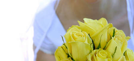 Wedding bride holds bouquet of yellow roses photo