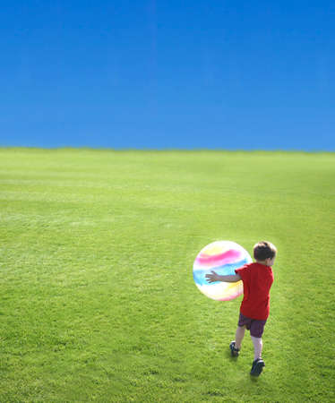 Young boy holding large ball as he walks on the green grass against the blue sky Stock Photo - 456892