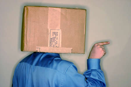 spunk: Business man wearing blue shirt has carboard box over his head as he is pointing out towards the side