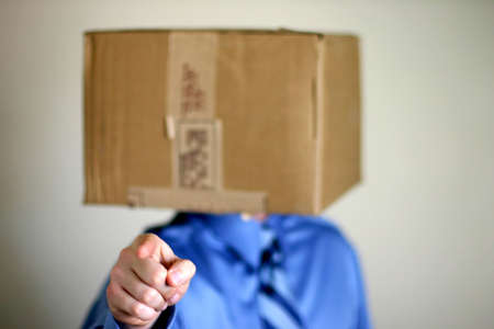 resourcefulness: Business man in blue shirt and blue tie has carboard box over his head as he is pointing towards you