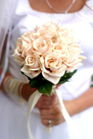 spousal: Bride in white dress is holding white flowers