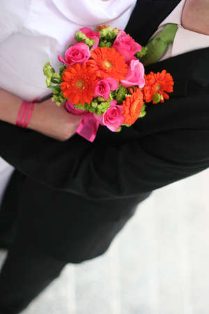 hitched: Bride and groom are holding each other with a bouquet of flowers in between them.