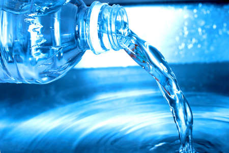 Water from a water bottle is being poured out into a metal container, Stock Photo