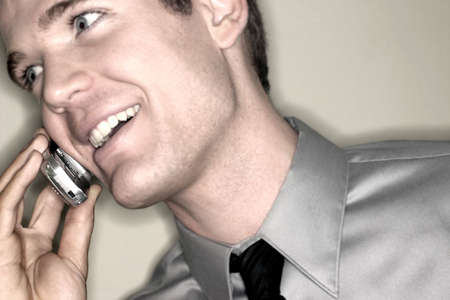Business man in gray shirt is talking on his cellphone Stock Photo