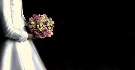 hitched: Bride is holding a beautiful bouquet arrangement against a long black backdrop