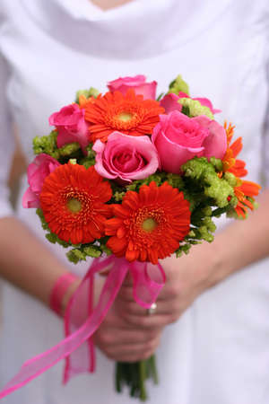 spousal: Bride is holding bouquet of different colors of flowers