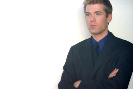 Blond hair, blue eye businessman is folding his arms and has focused look on his face Imagens