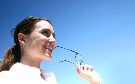 spunk: Negocios mujer se viste una camisa blanca y morder es su gafas.
