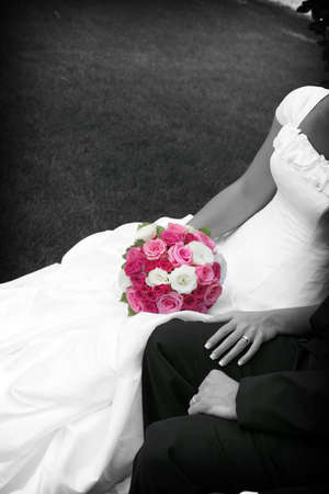 hitched: black and white of bride and groom with the pink bouquet highlighted and colored Stock Photo
