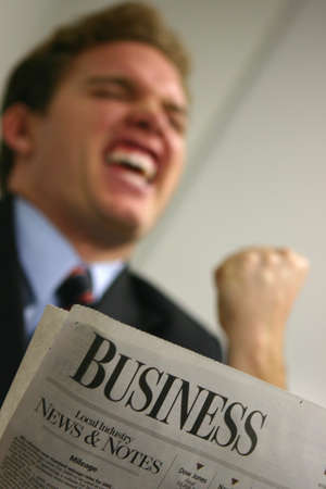 Business man in red tie and blue shirt holds fist close to his face as he expresses joy over reading the business section
