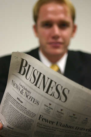 Blond hair business man is looking straight at you as he has the business section of the newspaper open Stock Photo