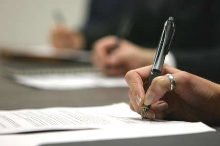 livelihood: contracts, pens, and hands on or next to a table Stock Photo