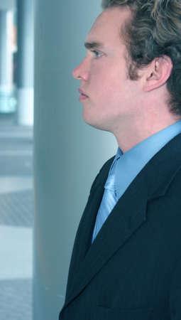 Brown hair businessman in blue suit is looking forward in an office building's hallway
